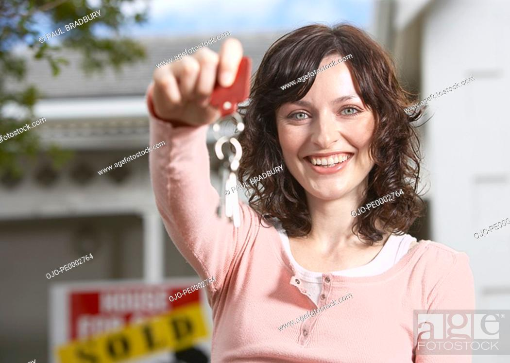Stock Photo: Woman with keys standing in front of house with sold sign.