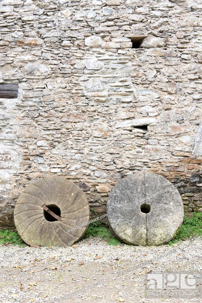 Stock Photo: Old millstones against a stone wall. Agorregi, Pagoeta Natural Park, Guipuzcoa, Spain.