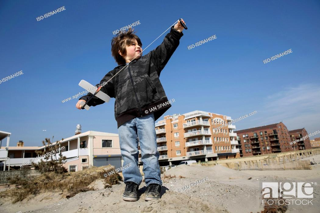 Imagen: Boy at the coast preparing to fly toy airplane, Long Beach, New York State, USA.