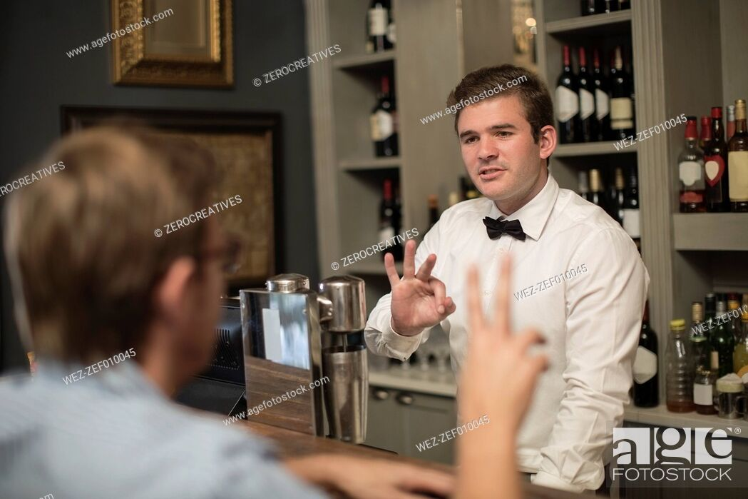 Stock Photo: Barkeeper behind bar taking an order.