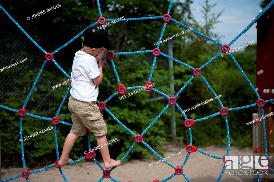 Imagen: Boy climbing on net in playground.