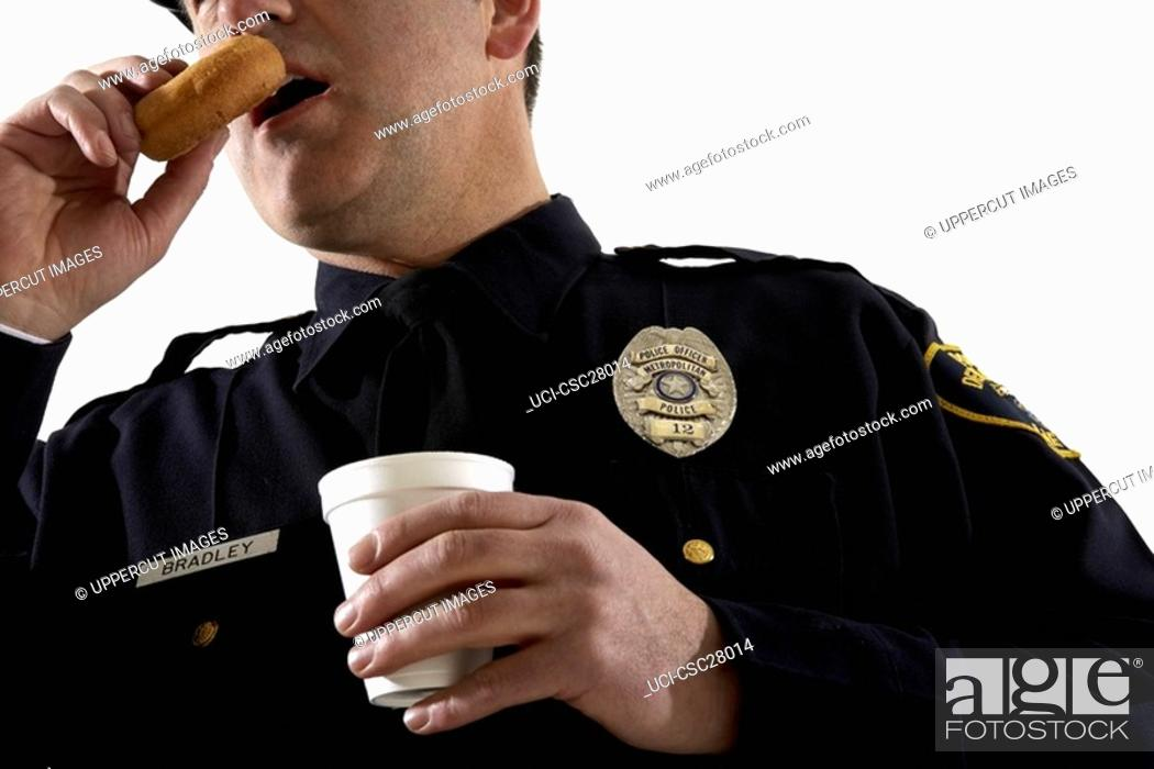 Stock Photo: Male police officer having coffee and a doughnut.
