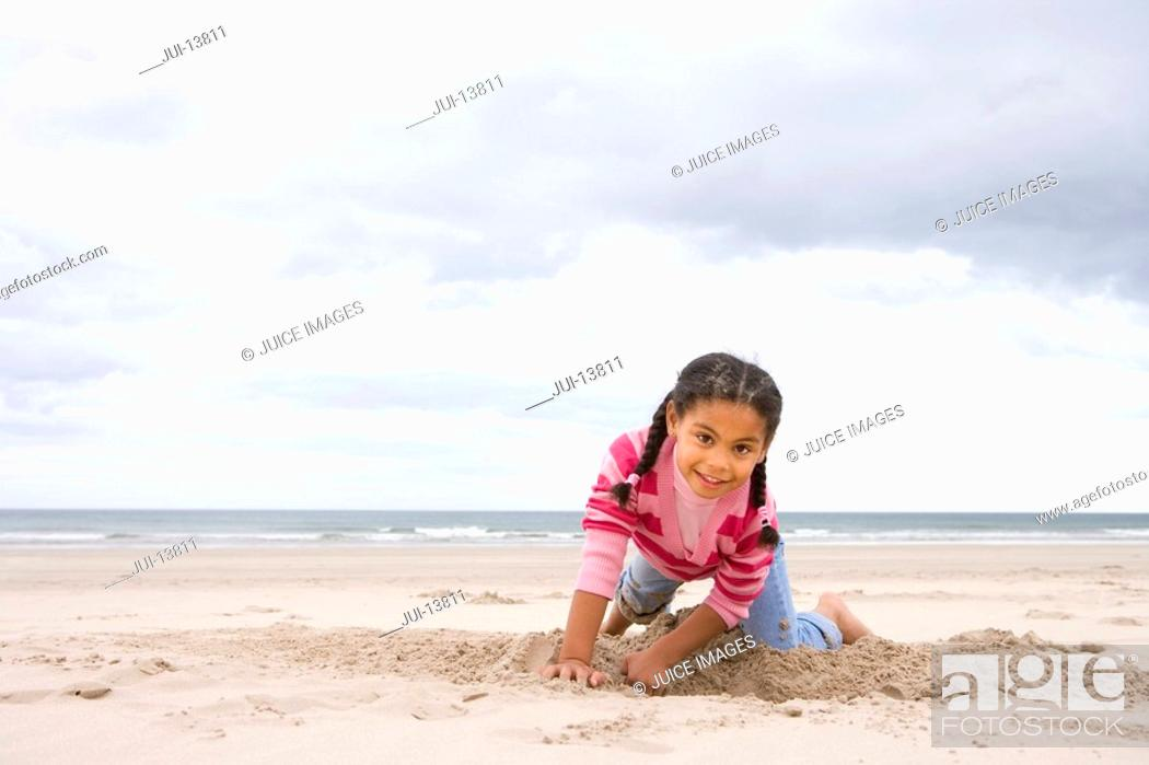 Stock Photo: Girl 5-7 digging hole on beach, smiling, portrait.