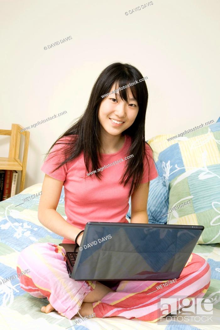 Stock Photo: Asian American teen working on laptop computer.