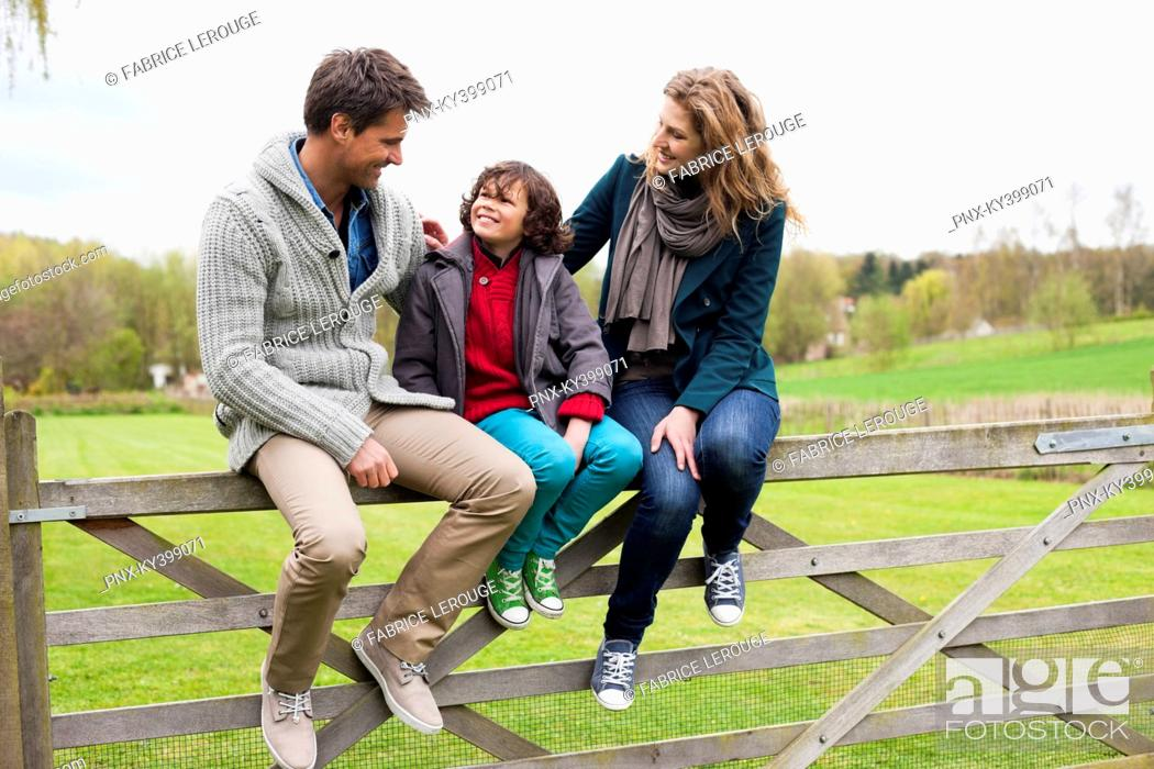 Stock Photo: Boy sitting with his parents on the gate of a cottage.