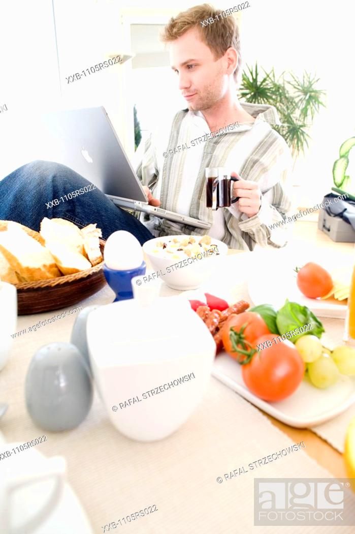 Stock Photo: man working on laptop during breakfast.