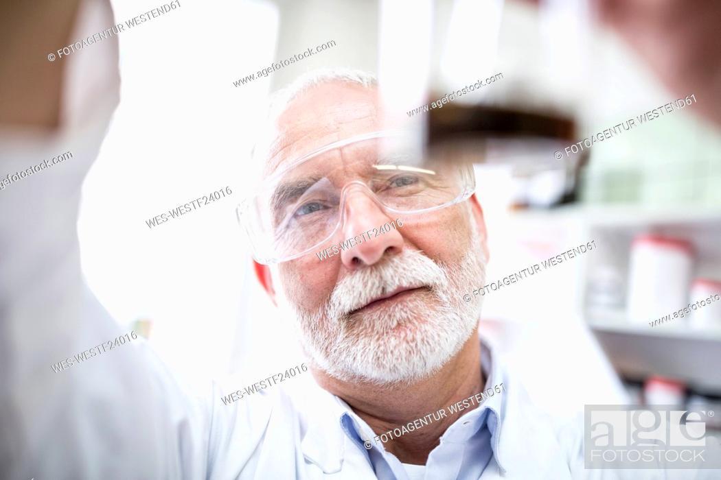 Stock Photo: Man looking at beaker in laboratory.