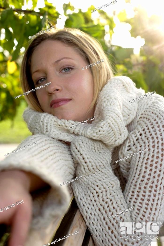 Stock Photo: Young woman in a cardigan on a wooden bench, close-up, selective focus.