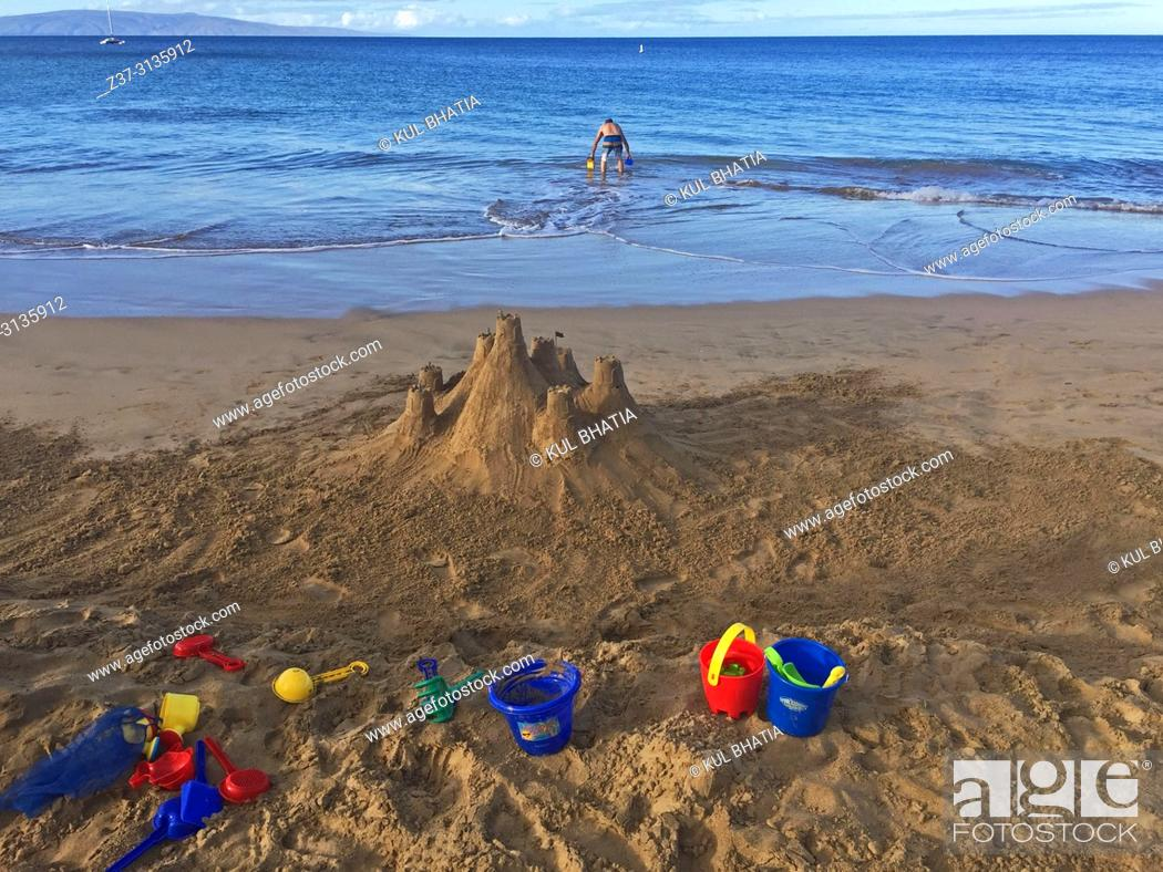 Stock Photo: A man wades into the water while a castle and tools are strewn about on the sand, sand, Charley Young Beach, S. Kihei, Maui, Hawaii, USA.