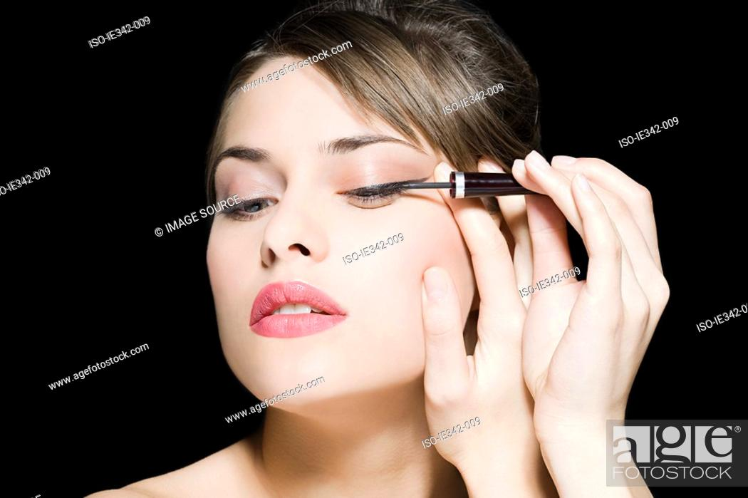Stock Photo: Woman applying eyeliner.