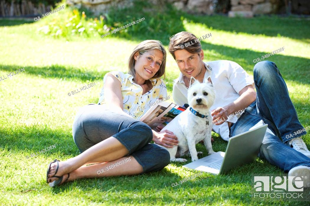 Stock Photo: Couple relaxing with dog in grass.