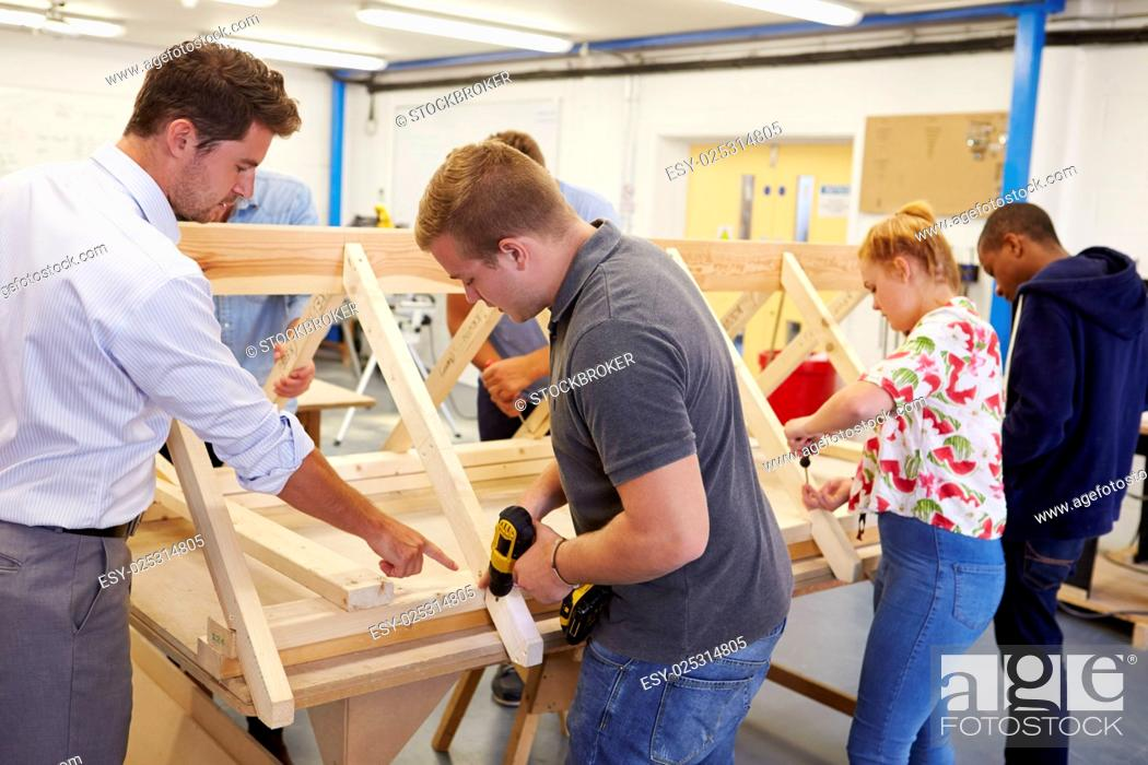 Stock Photo: Teacher Helping College Students Studying Carpentry.
