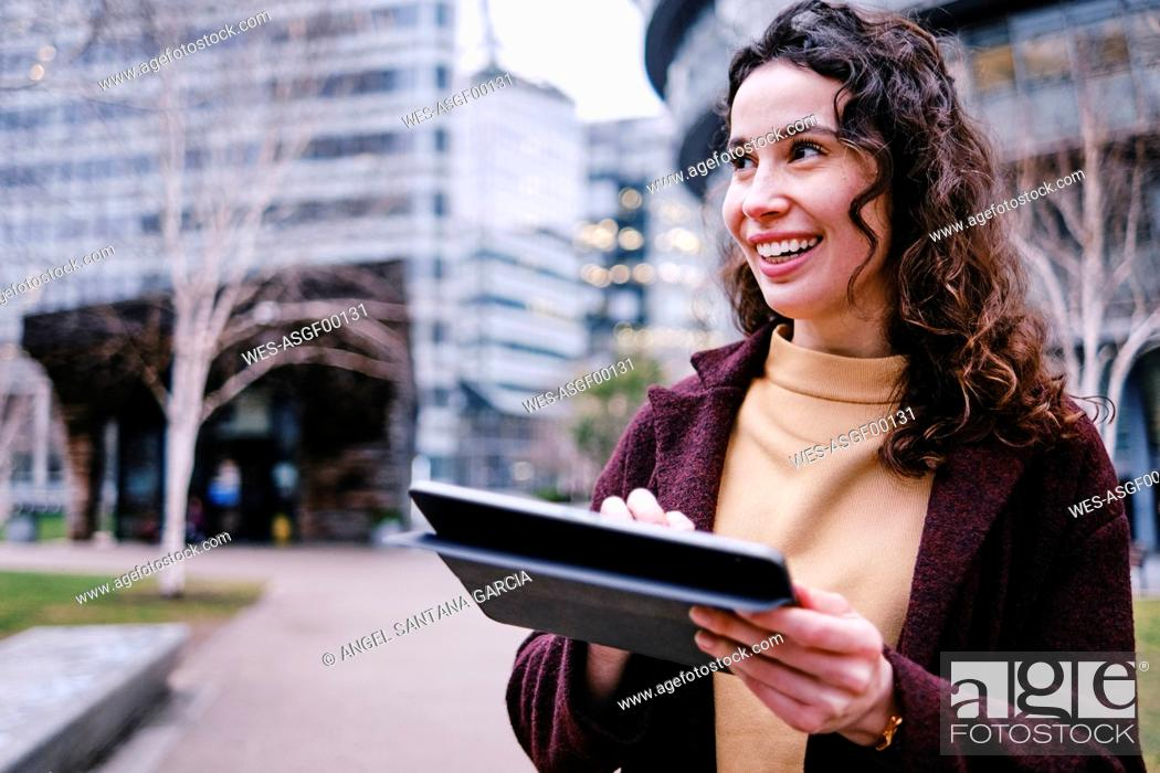 Stock Photo: Smiling female professional holding digital tablet while looking away.
