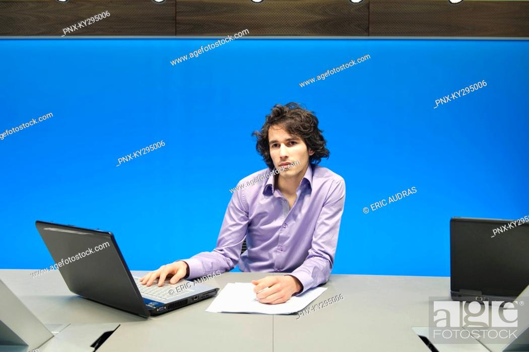 Stock Photo: Businessman working on a laptop in a conference room.