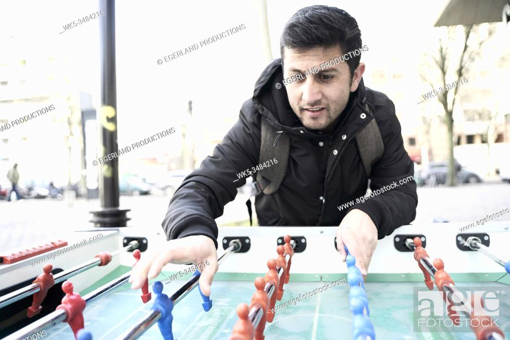 Stock Photo: Afghan man playing foosball, table soccer.