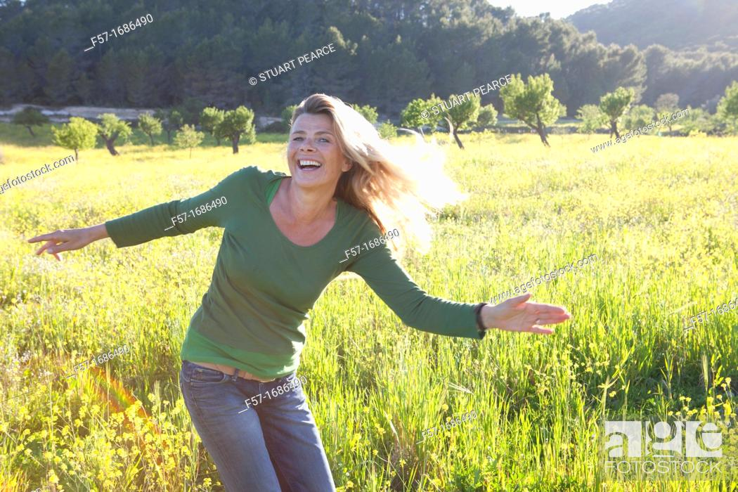 Stock Photo: Forty something year old woman in a meadow.