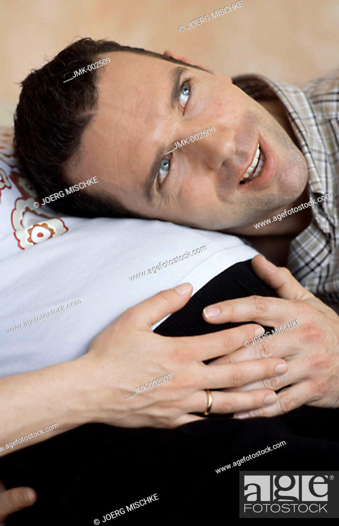 Stock Photo: A young man harking to his unborn child and a young pregnant woman, his wife, 25-30 30-35 35-40 years old.