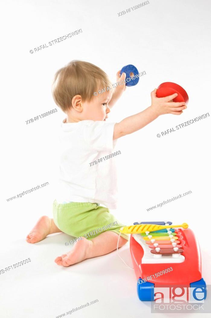 Stock Photo: baby boy playing on dulcimer.