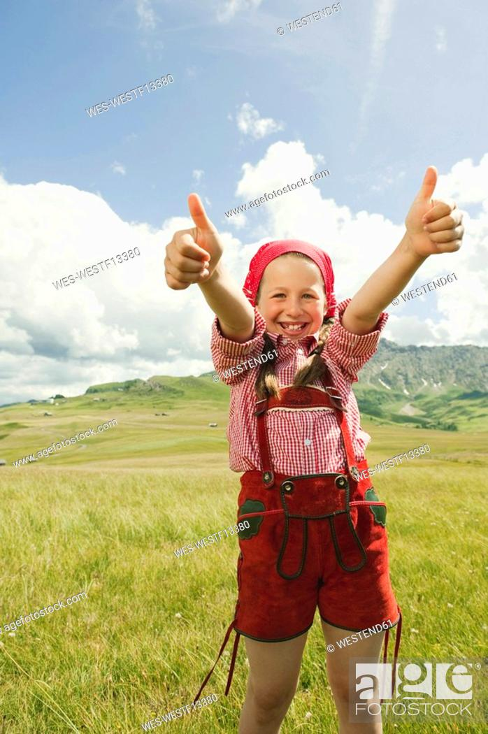 Stock Photo: Italy, Seiseralm, Girl 8-9 in meadow giving thumbs up, smiling, portrait.
