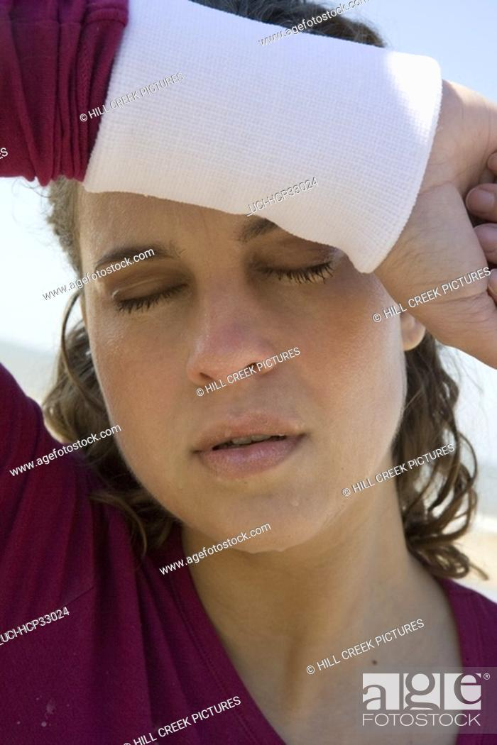 Stock Photo: Woman wiping brow with forearm.