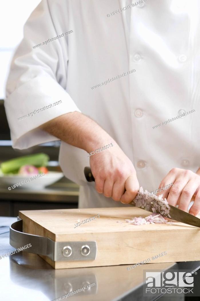 Stock Photo: Male chef chopping onion.