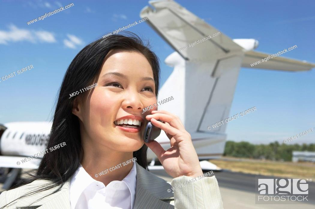 Stock Photo: Smiling Businesswoman standing outside Airplane talking on mobile.