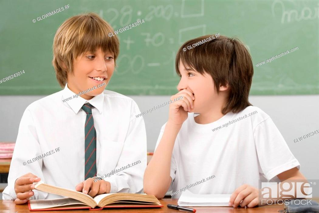 Stock Photo: Two schoolboys looking at each other and smiling in a classroom.