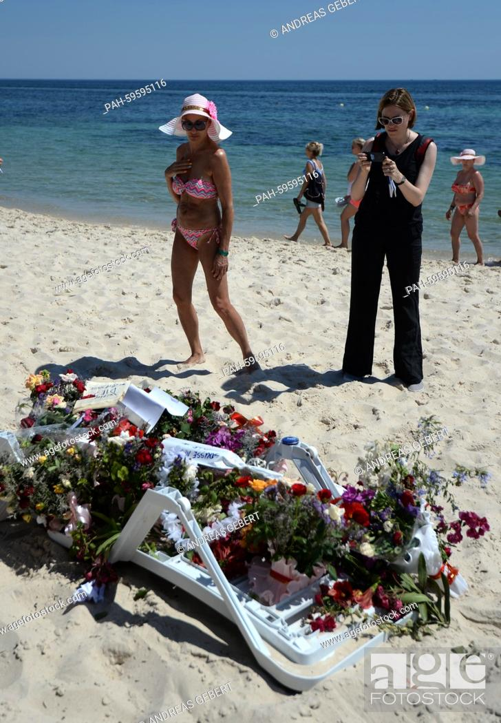 Two Tourists Stand In Front Of Numerous Flowers Laid Out On