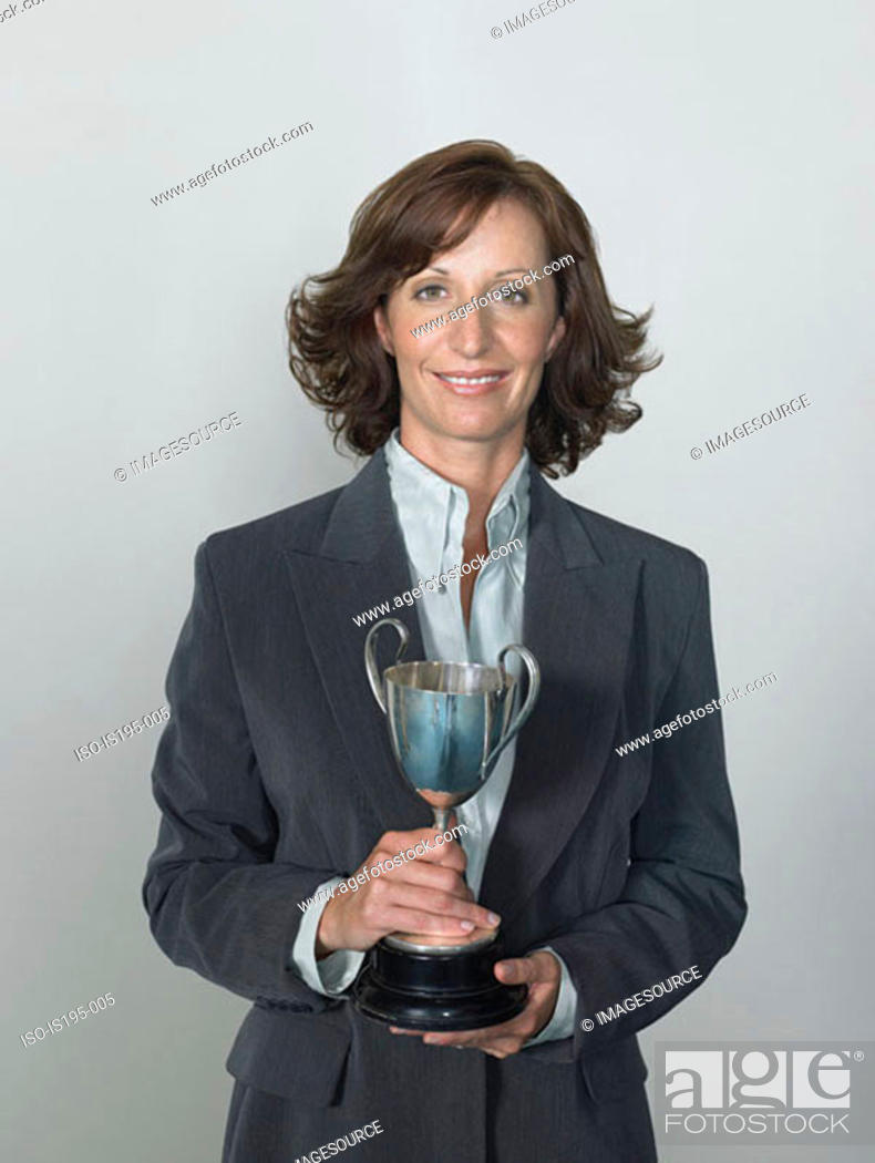 Stock Photo: Businesswoman holding a trophy.