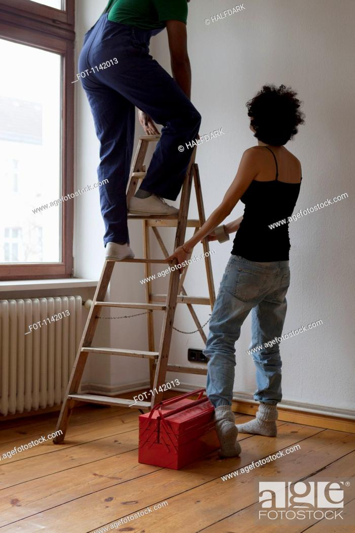 Stock Photo: A woman holding a ladder while a man steps up.