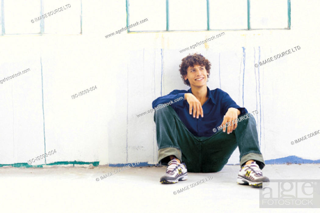 Stock Photo: Man sitting against fence.