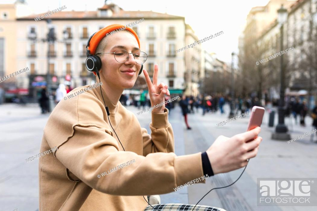 Stock Photo: Young woman taking a selfie while listening to music and making peace gesture with her hand.