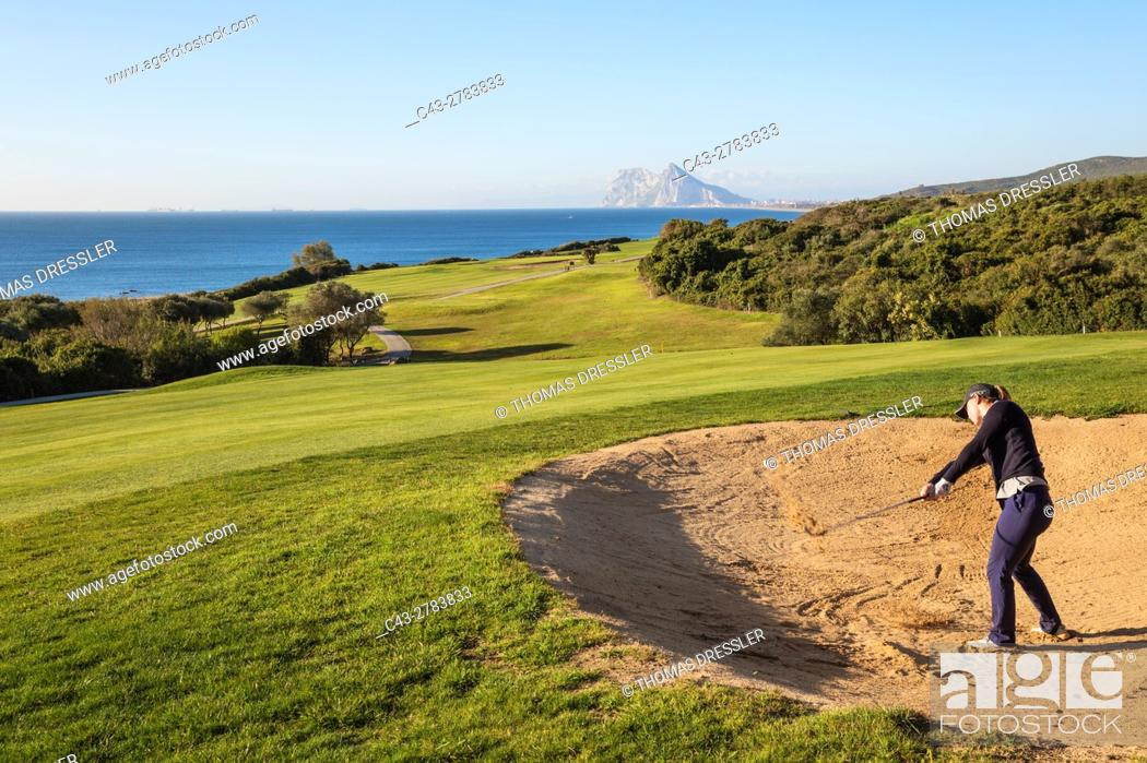 Stock Photo: Golfer at a bunker at the La Alcaidesa Golf Resort. In the background the Mediterranean Sea with the Rock of Gibraltar (British).