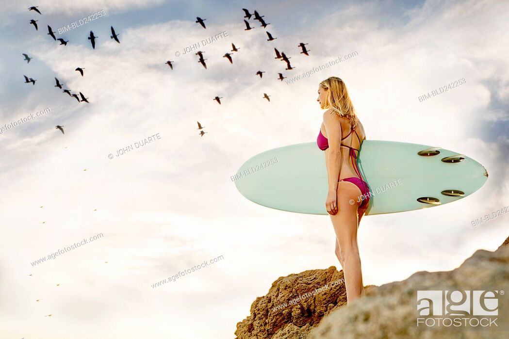 Stock Photo: Caucasian woman standing on rock holding surfboard.