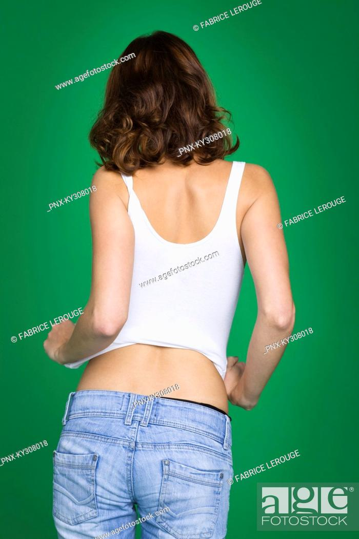 Stock Photo: Young woman in tank top and jeans, rear view.
