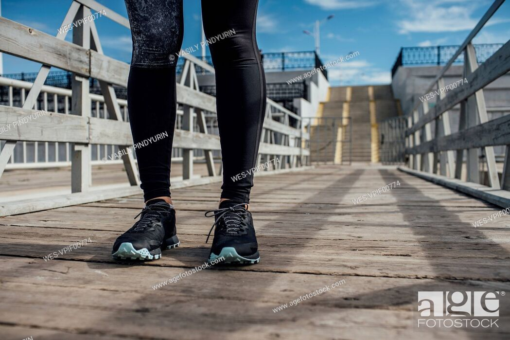 Photo de stock: Legs of athletic woman standing on a pier.