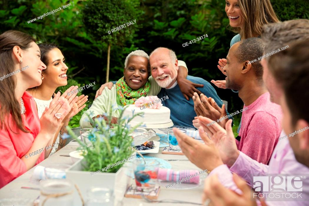 Stock Photo: Affectionate multi-ethnic senior couple hugging celebrating anniversary at patio table.