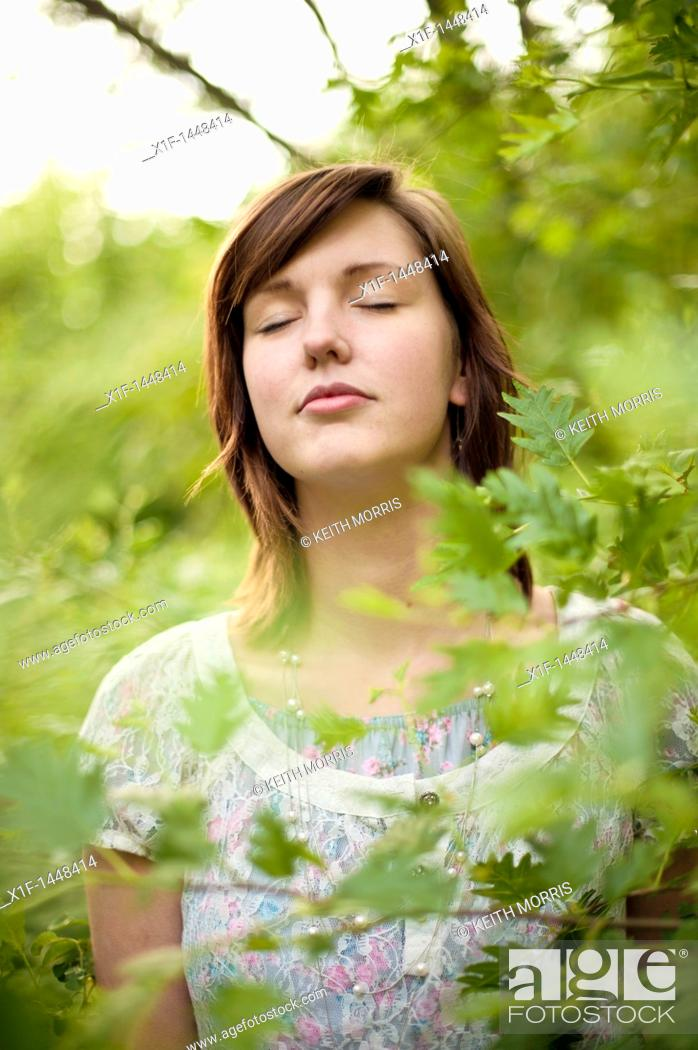 Stock Photo: A young slim attractive girl in her late teens or early 20's, outdoors in a woodland glade  with her eyes closed, UK.