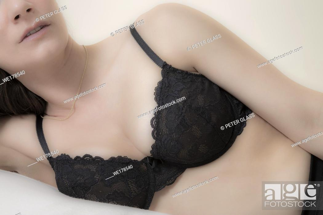Stock Photo: Young woman, wearing just a bra and her eyes hidden, lying on a bed.