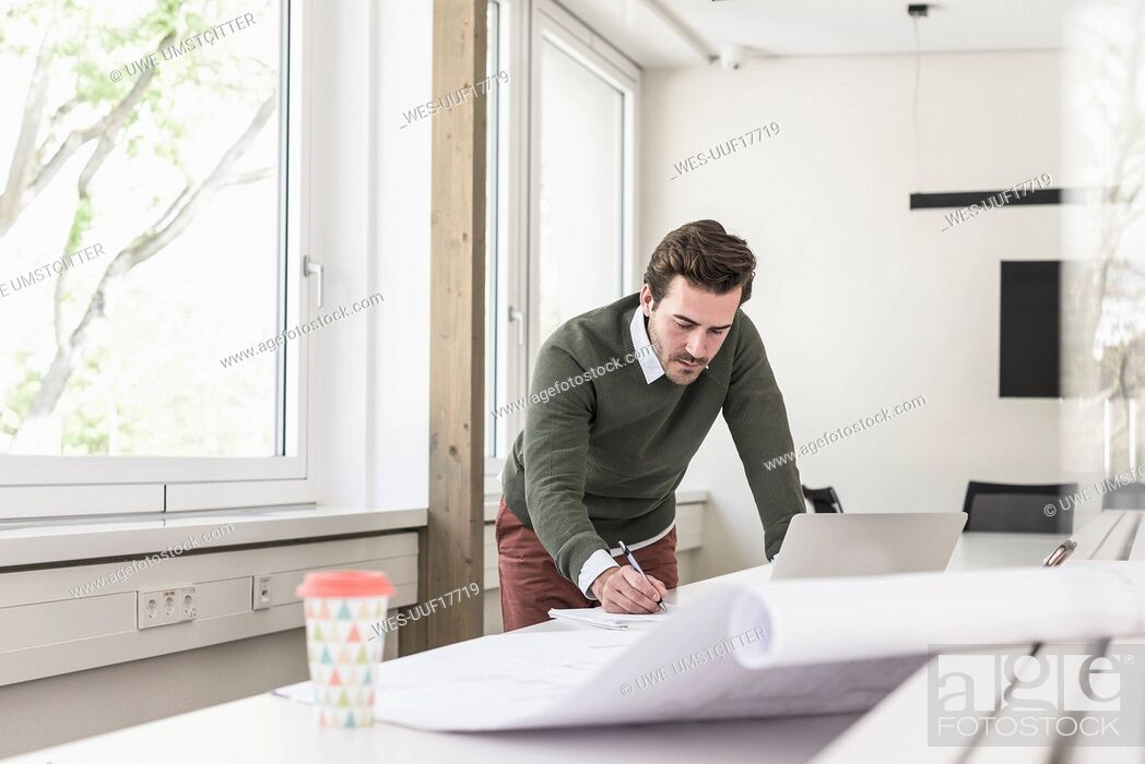 Stock Photo: Young architect working on blueprint in bright office.