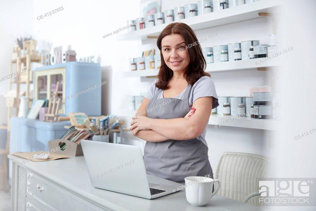Photo de stock: Portrait confident, smiling art shop business owner standing at counter.