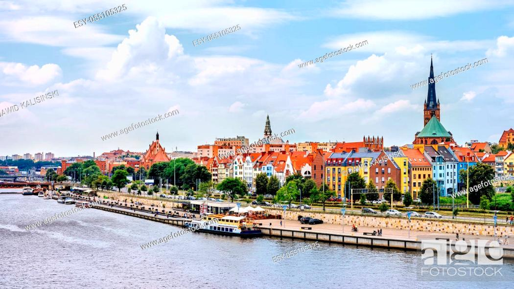 Stock Photo: Ships anchored on Odra River pier. People relaxing on Piastowski Boulevard. Cathedral Basilica of St James the Apostle in background, Szczecin, Poland.