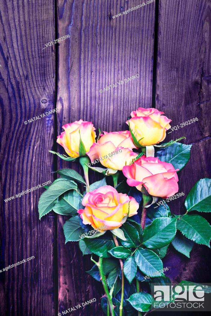 Stock Photo: Bouquet of blossoming roses on a brown wooden background, vintage toning.
