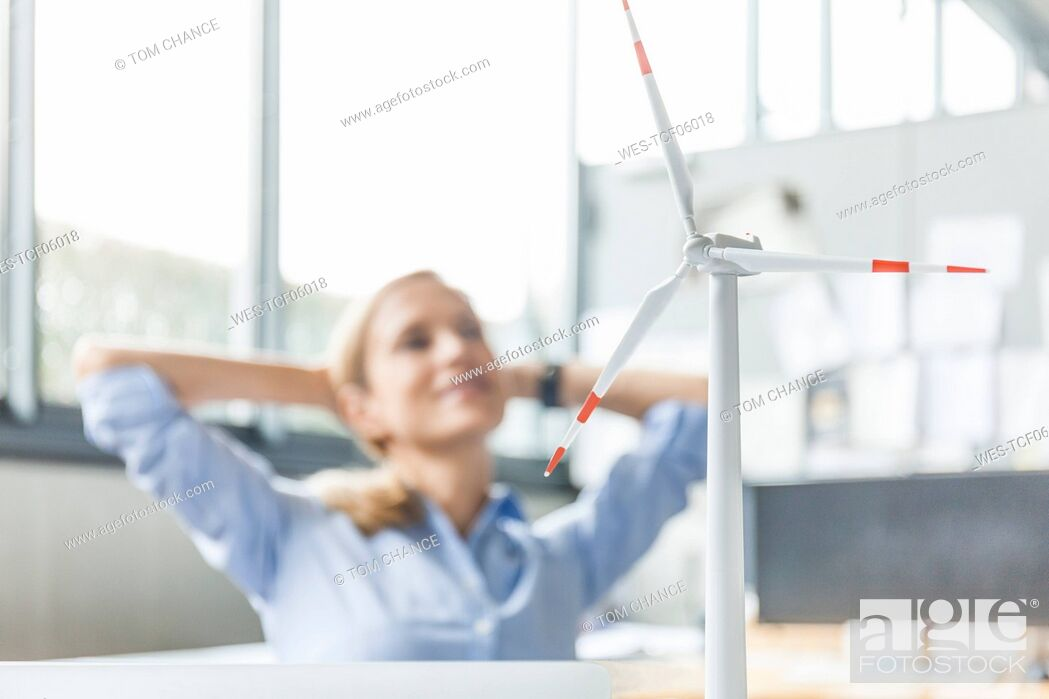 Stock Photo: Wind turbine model and woman in background in office.