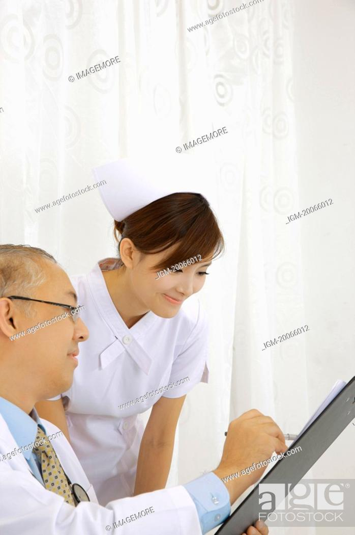 Stock Photo: Doctor and nurse looking at the clipboard together with smile.