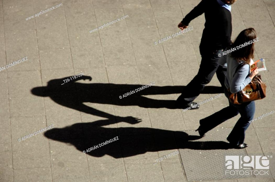 Stock Photo: A couple walking hand in hand with their shadows.