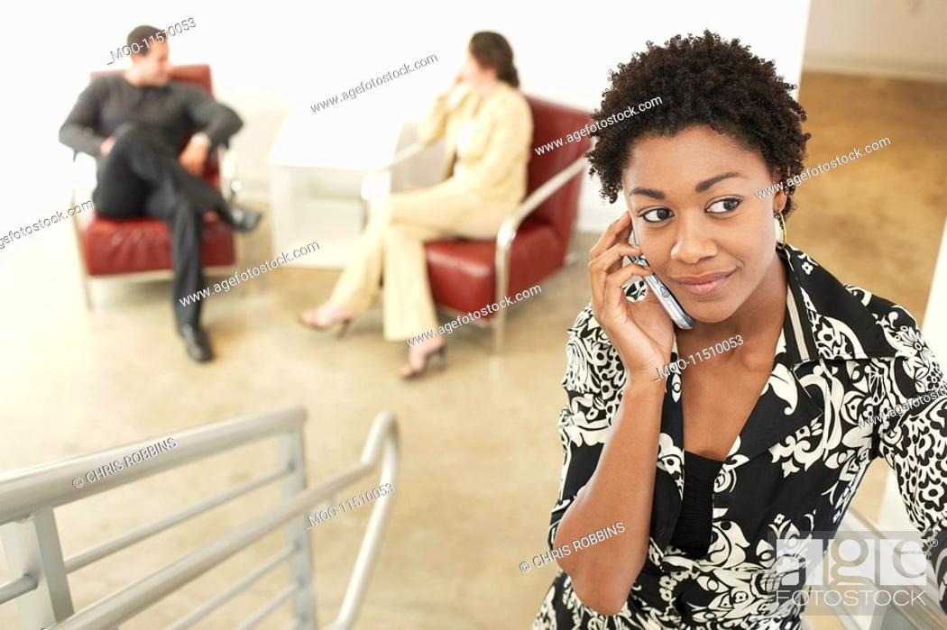 Stock Photo: Businesswoman using mobile phone on stairs.