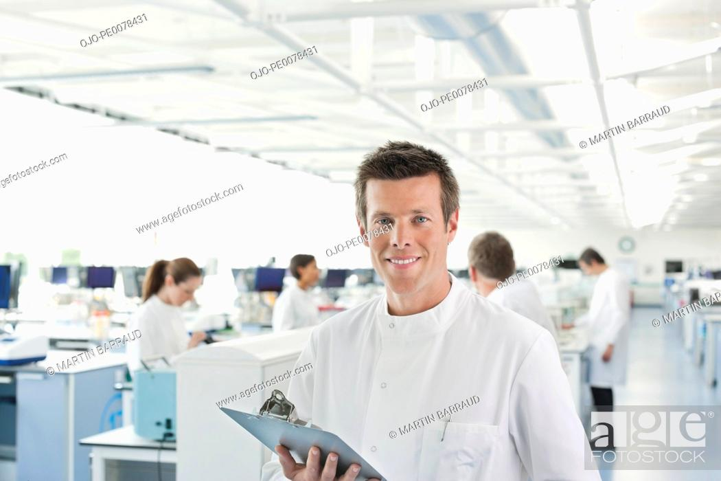Stock Photo: Scientist using clipboard in lab.