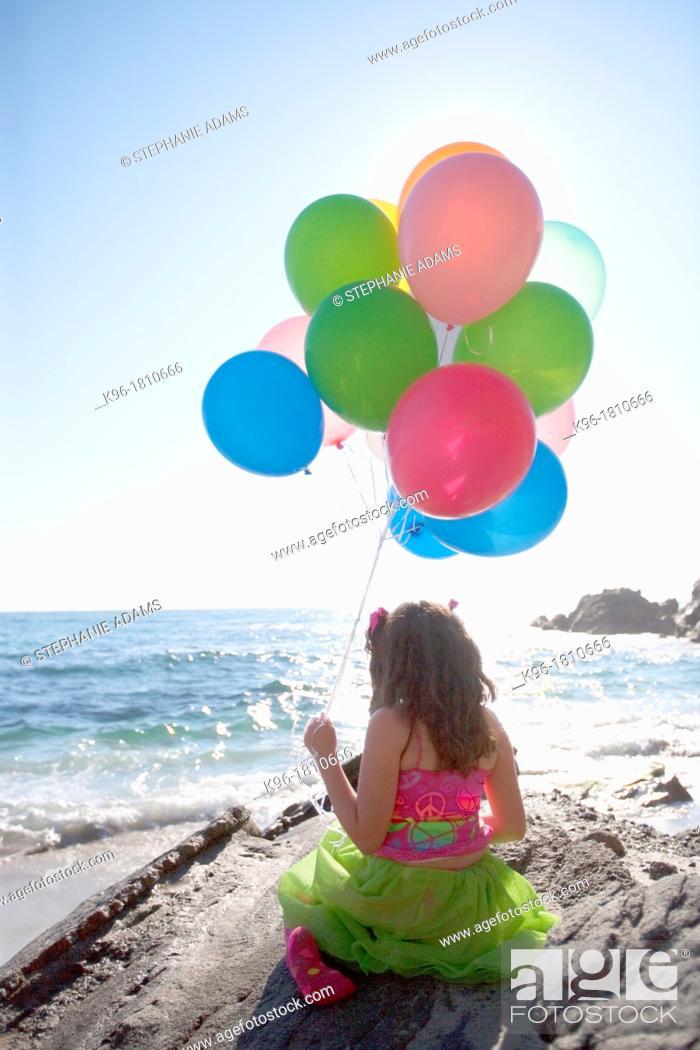 Photo de stock: little girl sitting on rocks, holding balloons, overlooking the ocean.