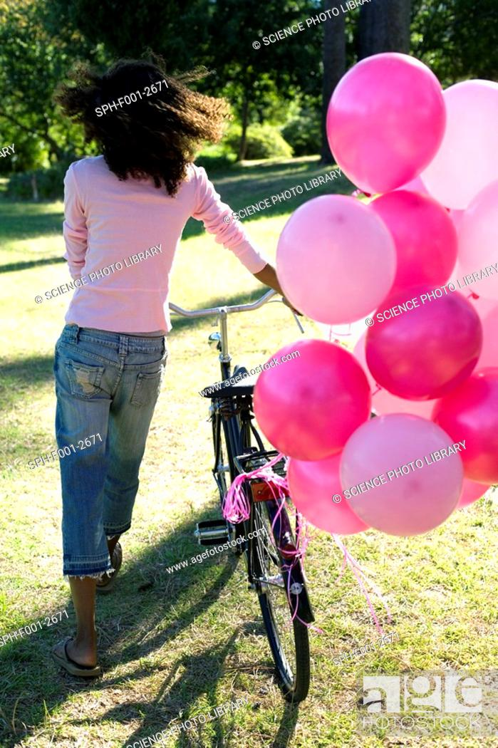 Stock Photo: Woman with a bicycle and balloons.